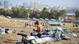 A homeless man washes himself on a field in District Six. Picture: Henk Kruger/ANA