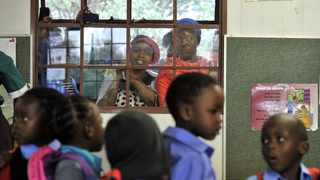 SAFE ZONE: Anxious parents looking on and taking pictures of their children through a window on their  first day at Mogale Primary School in Mamelodi. Picture: Oupa Mokoena