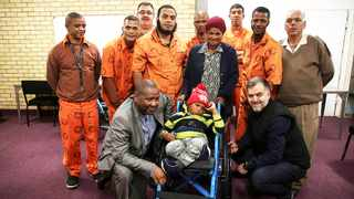 Western Cape regional commissioner Delekile Klaas with a group of five offenders hands over a wheelchair to five-year-old John Curtlin at the Goodwood Correctional facility as his mother looks  on.