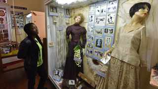 Staff member Vicky Mlanjeni admires a  display featuring weddings of the the past in the forced removals / Group Areas Act section of the Simon's Town Museum.  Picture: Jason Boud