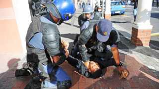 Two heavily armed policemen pin a student to the ground and choke him during a march to Parliament to demand the release of the Fees Commission report yesterday. Picture: Ayanda Ndamane/ANA