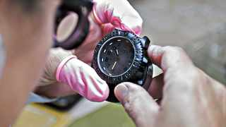 An employee inspects an assembled Luminox navy seal colormark 3050 series wristwatch at the Mondaine Watch Ltd. production facility in Solothurn, Switzerland, on Tuesday, Oct. 25, 2016. Mondaine is one of several Swiss watchmakers adding electronic functions to its watches as Apple Inc. encroaches into its territory. Photographer: Michele Limina/Bloomberg