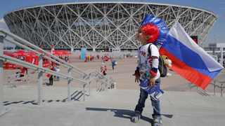 A young Russian soccer fan stands outside the Volgograd Arena. Photo: Sergei Ilnitsk/EPA