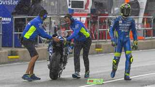 The body language says it all as Suzuki rider Andrea Iannone walks back to his pit while two Suzuki technicians push his GSX-RR out of the pouring rain. Picture: MotoGP.com