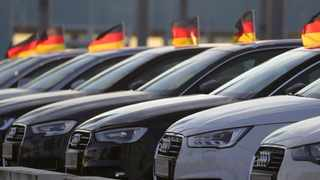 German national flags fly from used Audi AG automobiles on the forecourt of the automaker's showroom in Berlin, Germany, on Tuesday, June 19, 2018. Volkswagen AG named Bram Schot as interim chief at its Audi unit, selecting the luxury brand's sales chief to replace longtime leader Rupert Stadler following his arrest Monday over his role in VWs diesel-emissions cheating. Photographer: Krisztian Bocsi/Bloomberg