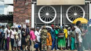 A Zimbabwean soldier watches shoppers lining up, in Bulawayo. Picture: AFP