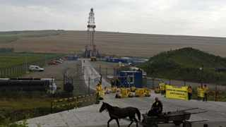 (File photo) A man rides a horse-driven cart in front of a Chevron drilling site for shale gas, which is blocked by Greenpeace activists during a protest, in the village of Pungesti, northeast Romania July 7, 2014. REUTERS/Bogdan Cristel