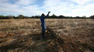 A worker gestures in front of acres of unused land in Zimbabwe. Picture: AP