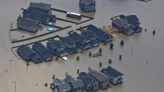 Houses are surrounded by flood waters in High River, Alberta, south of Calgary. Power outages in the Canadian oil capital of Calgary could last for weeks or even months, according to city authorities.
