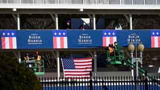 Workers place Biden-Harris inauguration banners on the inaugural parade viewing stand across from the White House in Washington, US. File picture: Reuters