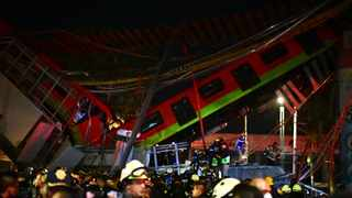 Rescue workers gather at the site of a metro train accident after an overpass for a metro partially collapsed in Mexico City. Photo: Pedro PARDO / AFP