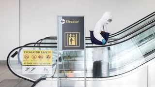 A woman wears personal protective equipment (PPE) rides an escalator at John F. Kennedy International Airport in New York