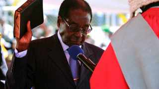 Zimbabwean President Robert Mugabe holds the Bible as he is sworn in for another five-year term. Photo: AP