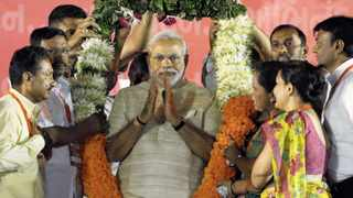 Hindu nationalist Narendra Modi, who will be the next prime minister of India, wears a garland presented to him by his supporters at a public meeting in the western Indian city of Ahmedabad on Tuesday. Modi fought back tears after sweeping to power. Photo: Reuters