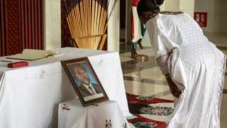 An unidentified dignitary pays her respects after signing the book of condolences in front of a photograph of the late President Pierre Nkurunziza, at the presidential palace in Bujumbura, Burundi Wednesday, June 10, 2020. Burundi's government said Tuesday, June 9, 2020 that President Pierre Nkurunziza had died of a heart attack. (AP Photo/Berthier Mugiraneza)
