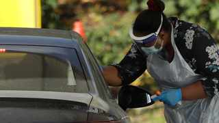 A person is tested for Covid-19 at a drive-through testing centre in a car park at Chessington World of Adventures, in Chessington, Greater London. Picture: Matt Dunham/AP