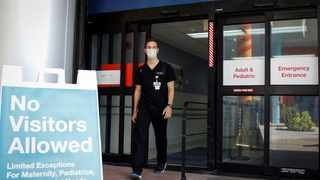 Dennis D'Urso, a resident ER doctor at Jackson Memorial Hospital in Miami, walks through a door during his shift. Picture: Marco Bello/Reuters