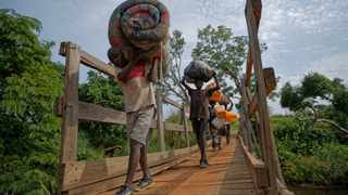 South Sudanese refugees cross a wooden bridge from South Sudan to Uganda at the Busia crossing, near Kuluba, in northern Uganda. File picture: Ben Curtis/AP