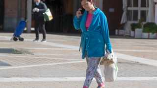 A woman carries a shopping bag after leaving a supermarket in Madrid, Spain. Picture: AP Photo/Paul White