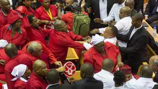 Members of the Economic Freedom Fighters (EFF), in red, clash with members of South African security forces after being ordered out of the National Assembly by the speaker of parliament during the State Of the Nation Address in Cape Town. EPA/RODGER BOSCH/POOL