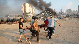 Civilians carry a victim at the explosion scene that hit the seaport, in Beirut Lebanon. Picture: Hussein Malla/AP