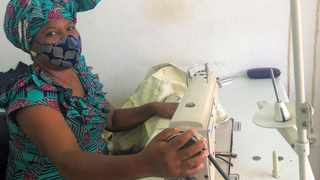 Jacqueline Zandamela sits at her sewing station in her shop in Maputo, Mozambique. Photo: UNHCR/Juliana Ghazi