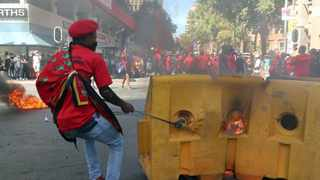 A man dressed in EFF regalia sets fire to the City's infrasture in Braamfontein during the continuous Wits students protests. Picture: Timothy Bernard/ African News Agency (ANA)
