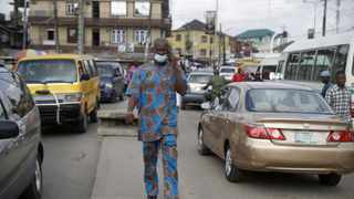 A man wearing a face mask to protect against coronavirus walk on the street in Lagos, Nigeria Picture: Sunday Alamba/AP