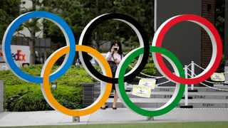 FILE PHOTO: A woman wearing a protective mask amid the coronavirus disease outbreak in 2020, takes a picture of the Olympic rings in front of the National Stadium in Tokyo. Photo: Kim Kyung-Hoon//Reuters