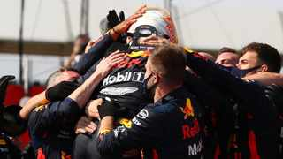 Red Bull driver Max Verstappen is swamped by his team after his win at Silverstone. Picture: Bryn Lennon/AP