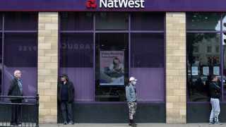 FILE - People maintain social distance while they queue outside a Natwest bank in Wimbledon in London, Britain, May 1, 2020. Photo: Hannah McKay/Reuters