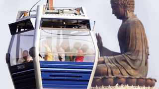 A cable car passes the Buddha statue overlooking Po Lin Monastery at Hong Kong's Lantau Island, on the open day of the cable car service, September 18, 2006. REUTERS/Paul Yeung (HONG KONG)