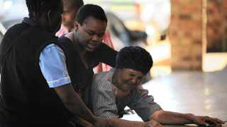 12/11/2013 Emotional family members of the Moloto road bus accident weep after identifying the bodies of their lkoved ones at the KwaMhlanga hospital morgue. Picture: Phill Magakoe