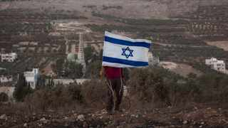 Back-dropped by the West Bank village of Burin, a Jewish settler holds an Israeli flag near the Jewish settlement of Yitzhar, near Nablus. File picture: Oded Balilty/AP