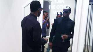 American rapper P Diddy looks at a sculpture by Haroon Gunn-Salie on forced removals and land, which he has bought for his home.