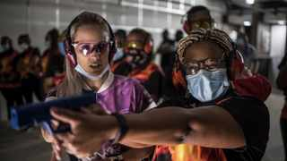 A South African woman learns to control her weapon while others gather at the lower end of a shooting range as they take part in a training organised by the women empowerment group Girls on Fire, in Midrand. Picture: Marco Longari/AFP