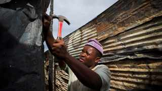 A man rebuilds his shack with both burned and new iron sheets after a fire in Masiphumelele, Cape Town. File picture: Nic Bothma/EPA
