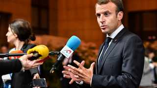 French President Emmanuel Macron talks with journalists as he leaves an EU summit in Brussels, early Friday, June 29, 2018. (AP Photo/Geert Vanden Wijngaert)