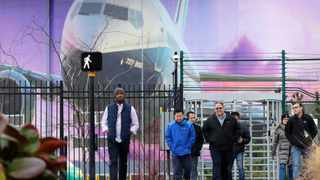 Boeing workers exit the plant in front of a giant mural of a jet on the side of the manufacturing building behind, in Renton, Washington. Picture: Elaine Thompson/AP