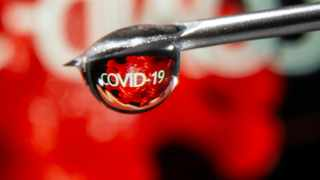 """COVID-19"""""""" is reflected in a drop on a syringe needle in this illustration taken November 9, 2020. REUTERS/Dado Ruvic/Illustration"""