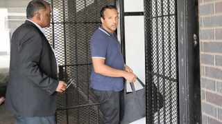 Avineshsing Rajbansi being led into the holding cells by the arresting officer, Lieutenant-Colonel V C Pillay.