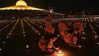 Buddhist monks light 330 000 candles in an attempt to break the Guinness World Record for the largest flaming image during Earth Day celebrations at the Wat Dhammakaya Buddhist temple on the outskirts of Bangkok. Picture: Lillian Suwanrumpha/AFP