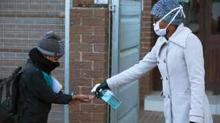 A pupil's hands are sanitised on returning to school in Johannesburg as more learners were permitted to return to class. Picture: Denis Farrell/AP