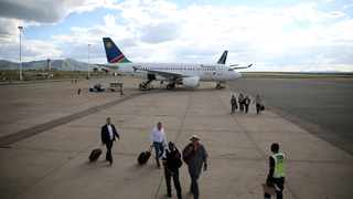 FILE PHOTO: Passengers walk past an AirNamibia aircraft at the Hosea Kutako International Airport, outside Windhoek in Namibia. The airport will reopen on September 1.