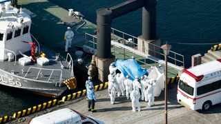 Medical workers in protective suits lead a passenger tested positive for a new coronavirus from the cruise ship Diamond Princess at Yokohama Port last year. Picture: Hiroko Harima/Kyodo News via AP