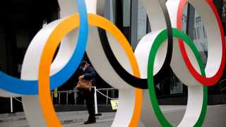 FILE PHOTO: A man wearing a protective mask against Covid-19 is seen through the Olympic rings in Tokyo, Japan. Photo: Issei Kato/Reuters