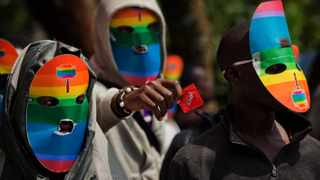 In a file photo, Kenyan gays and lesbians and others supporting their cause wear masks to preserve their anonymity and one holds out a wrapped condom, as they stage a rare protest, against Uganda's increasingly tough stance against homosexuality outside the Uganda High Commission in Nairobi. Picture: Ben Curtis