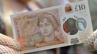 People in period costume display the new £10 note featuring Jane Austen, which marks the 200th anniversary of Austen's death, during the unveiling at Winchester Cathedral, England, Tuesday, July 18, 2017. (Chris J Ratcliffe/PA via AP)