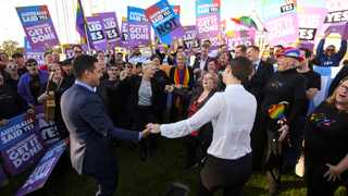 Same-sex marriage campaigners and volunteers cheer as they call on politicians to pass marriage equality legislation during rally outside Parliament House in Canberra, Australia. Picture: Lukas Coch/AAP Image via AP