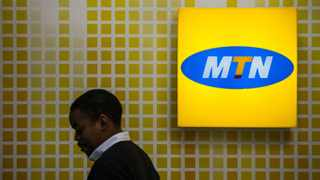 An employee passes an illuminated MTN logo on display inside an MTN Group Ltd. telecommunications store in the Hyde Park district of Johannesburg, South Africa, on Wednesday, Aug. 5, 2015. Photographer: Waldo Swiegers/Bloomberg